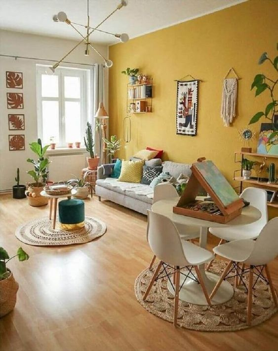 47 a welcoming boho living room with a mustard wall, neutral furniture, pretty artworks and potted plants
