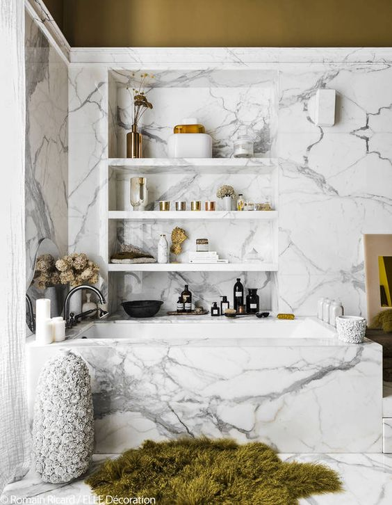 an eye catchy modern bathroom with white marble, a niche with shelves, a bright rug and dried blooms