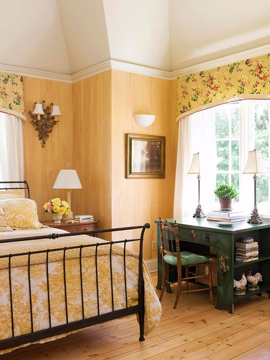 a country bedroom with yellow walls, a forged bed, yellow floral bedding and matching curtains plus a green desk