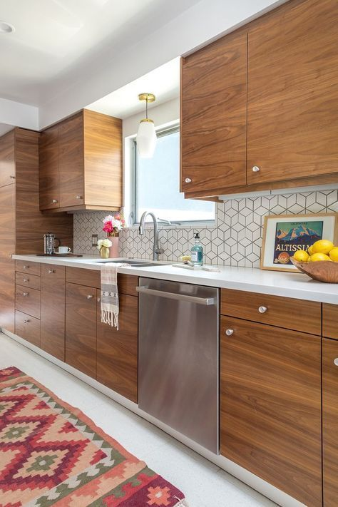 a mid-century modern walnut kitchen with small knobs, white geometric tiles ont he backsplash and white countertops