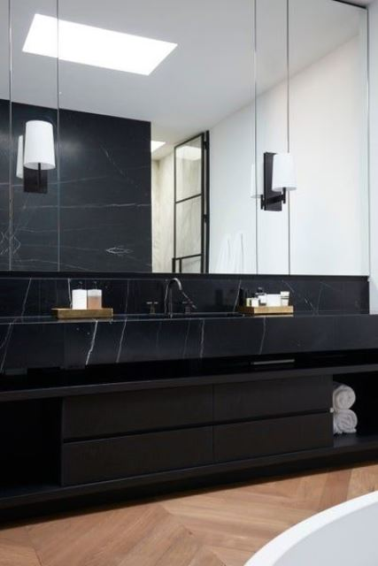 a refined contemporary bathroom with a black marble vanity, large mirrors and a skylight plus a bathtub