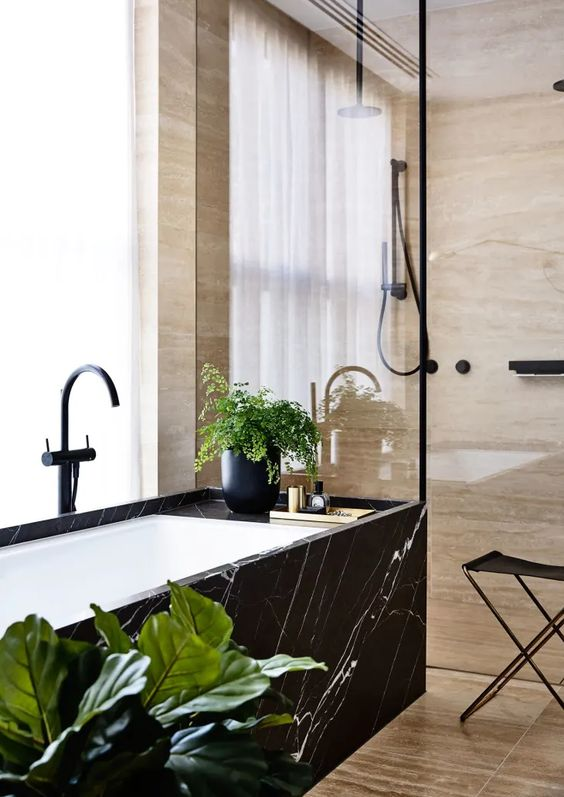 a beautiful bathroom with wood print tiles and a bathtub clad with black marble plus potted greenery