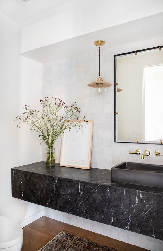 a modern bathroom with white walls, a black marble slab vanity and a black sink plus a large mirror