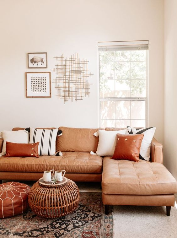 50 a neutral living room with a terracotta leather sectional, a leather and rattan ottoman and printed pillows