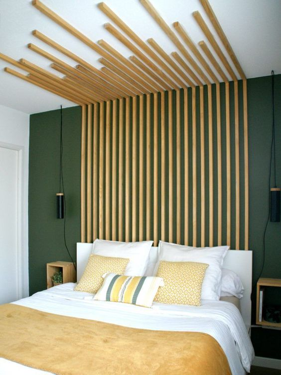 a statement modern bedroom with a grey wall, a white bed with an extended wooden slab headboard and yellow bedding
