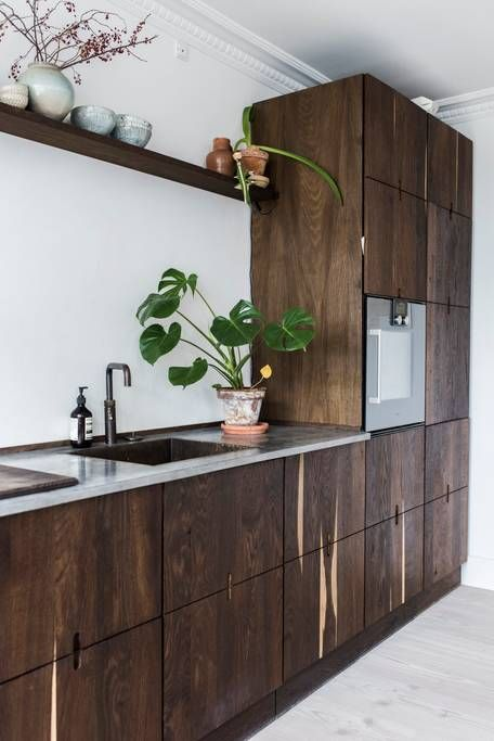 a unique Scandinavian walnut kitchen with sleek cabinets, black fixtures and grey stone countertops looks bold
