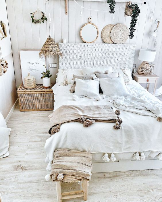 a coastal boho bedroom with a rattan bed, a chest, rattan lamps and coasters and greenery