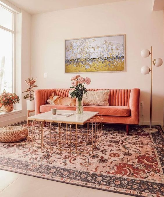 a cozy warm living room with a coral sofa, a printed rug, a copper table and a bold artwork