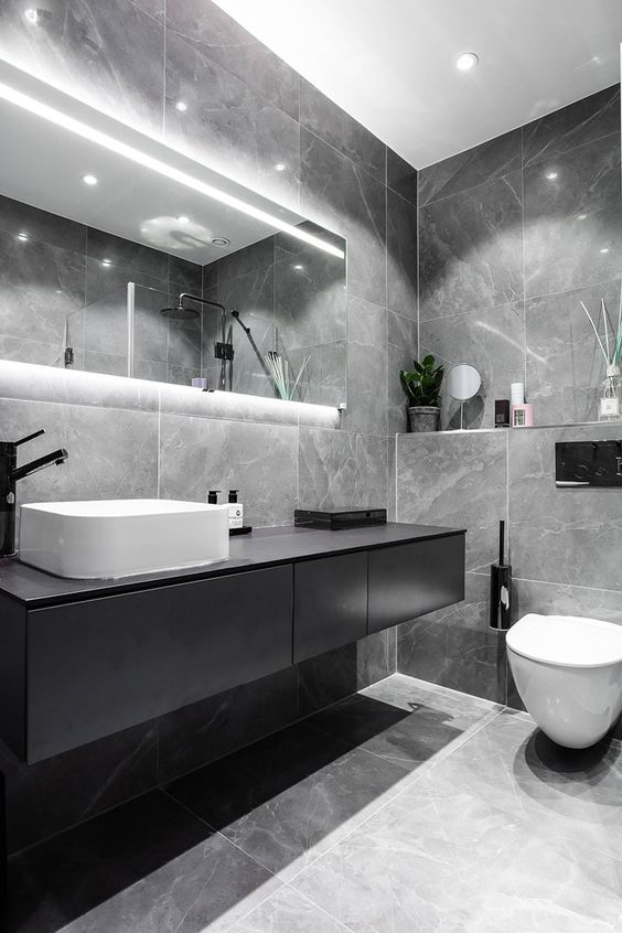 an elegant grey marble tile bathroom, a black floating vanity and a lit up mirror plus white appliances
