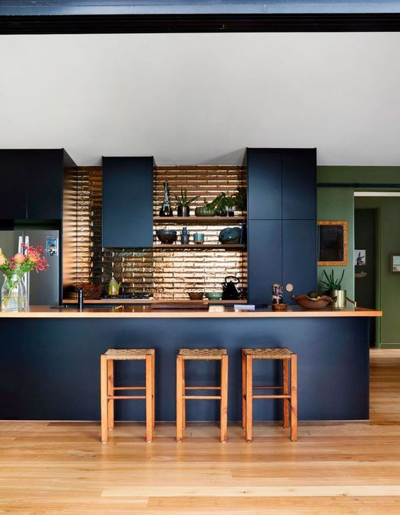 a chic and beautiful navy kitchen with sleek cabinets, tan countertops and a shiny copper tile backsplash