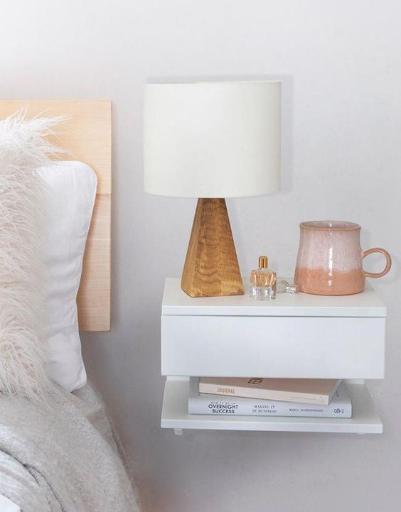 a floating nightstand with a drawer and an open shelf is a lovely idea to save some floor space