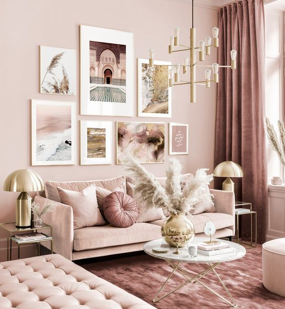 a refined monochromatic pink living room with elegant furniture, a gold chandelier, pampas grass and a cool gallery wall