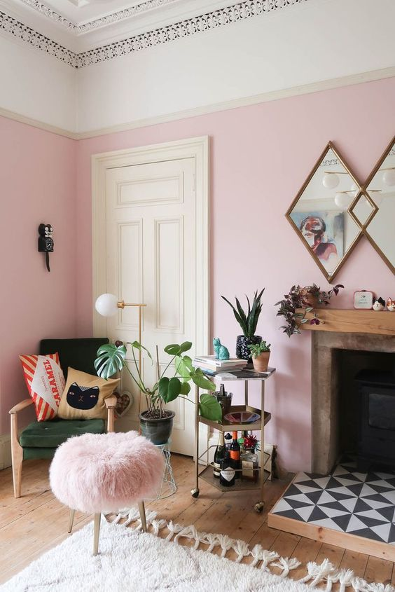 53 a cheerful pink living room with a green chair, a pink stool, a fireplace with tiles and potted plants