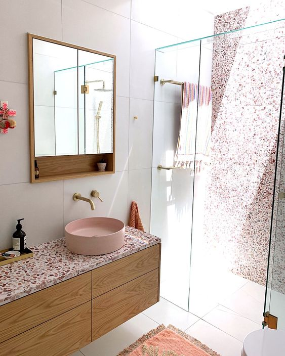 a chic contemporary bathroom with a pink terrazzo wall in the shower, a floating vanity with a pink terrazzo countertop plus a pink sink