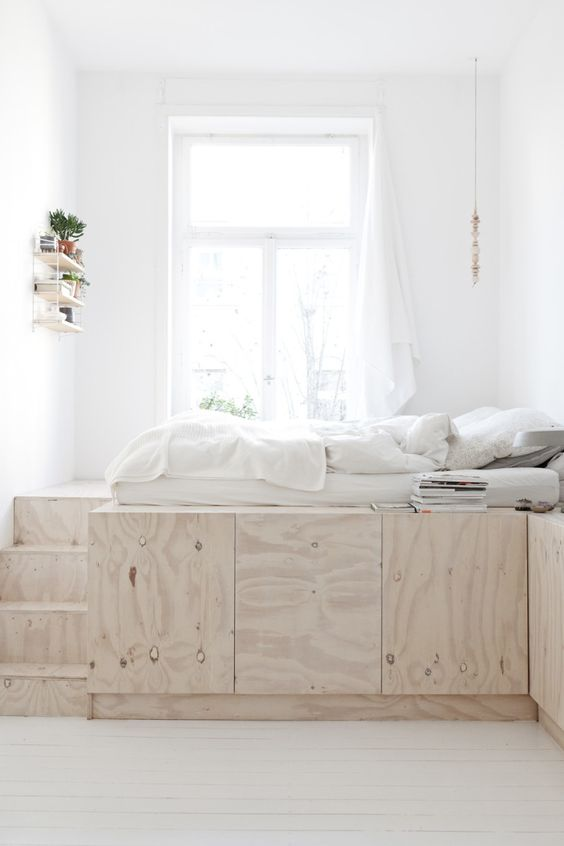 a minimalist bedroom in white with a storage platform that doubles as a bed doesn't have any clutter