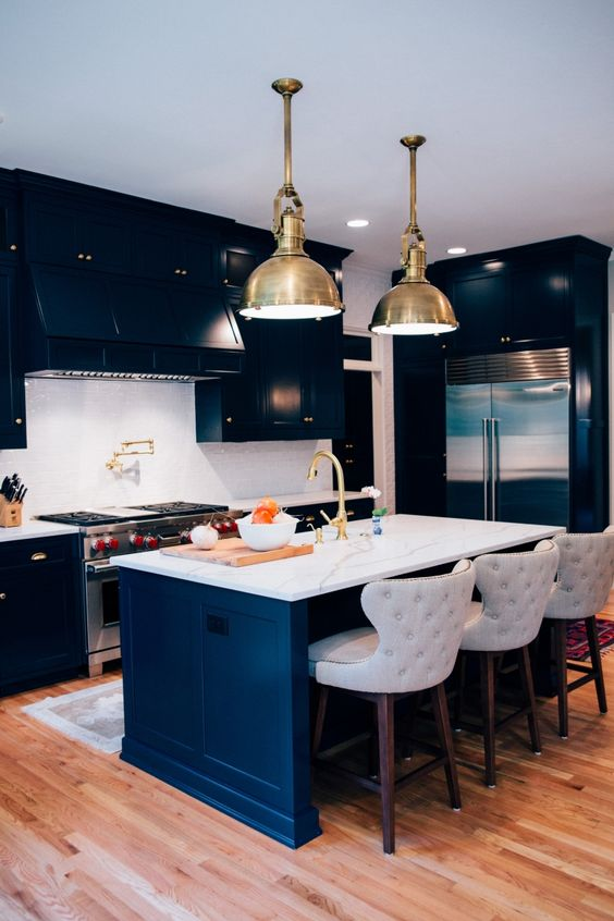 a stylish modern navy kitchen with a white stone backsplash and countertops, gold touches and pendant lamps