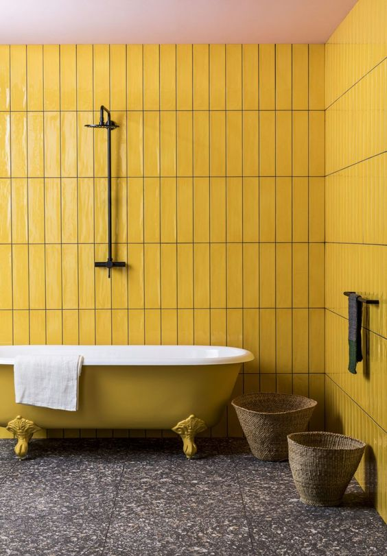 a bright yellow bathroom with skinny tiles, a clawfoot bathtub, a grey terrazzo floor is very catchy and bold