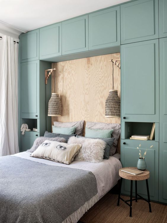 a chic small bedroom with a whole wall taken by a green storage unit, a plywood wall, sconces and cork stools is very cool