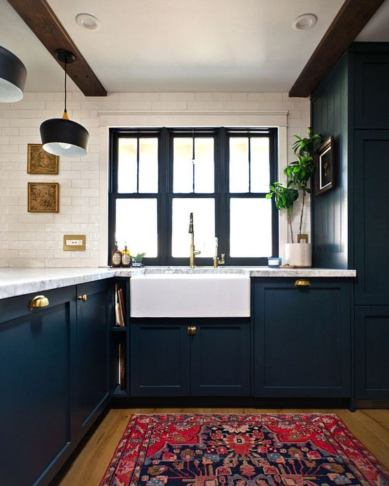 an elegant navy farmhouse kitchen with white stone countertops, a white tile backsplash and dark wooden beams on the ceiling