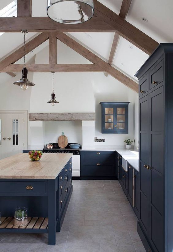 a beautiful navy farmhouse kitchen with vintage cabinets, white countertops and a large kitchen island plus a butcherblock countertop on it