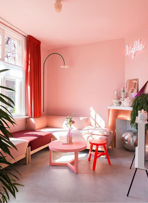 55 a bright and fun pink living room with a sectional, a non-working fireplace, a neon sign and colorful furniture