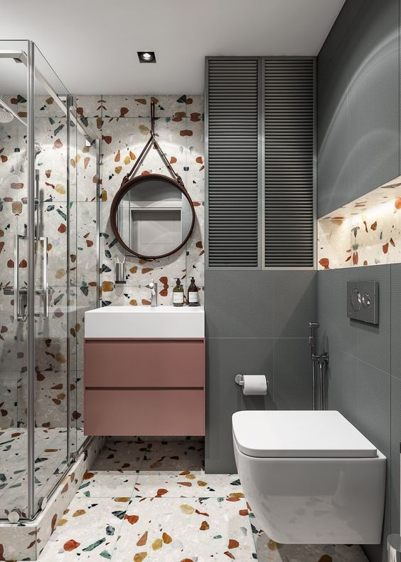 a contemporary bathroom with bright terrazzo walls and a floor, grey tiles, a mauve vanity and white appliances