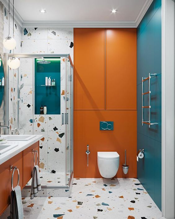 a colorful bathroom with blue and orange touches, terrazzo and white appliances and built in lights