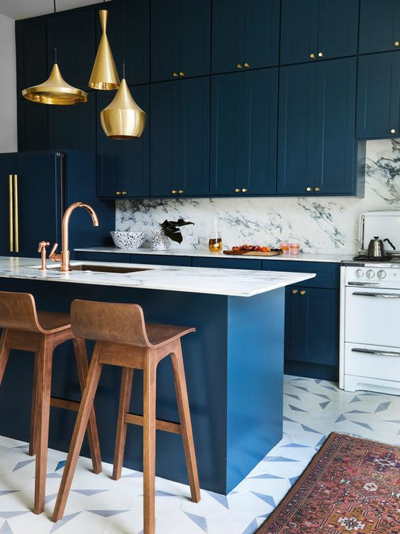 a glam navy ktichen with a white stone backsplash and countertops, a matching kitchen island and gold pendant lamps
