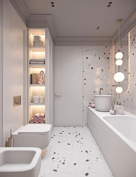 a neutral bathroom with neutral terrazzo walls and a floor, built-in lights and pink and blush touches