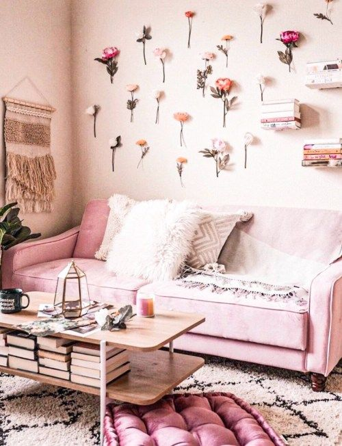 57 a pink living room with light pink walls, a bright pink sofa and an ottoman, flowers attached to the wall and a wooden table