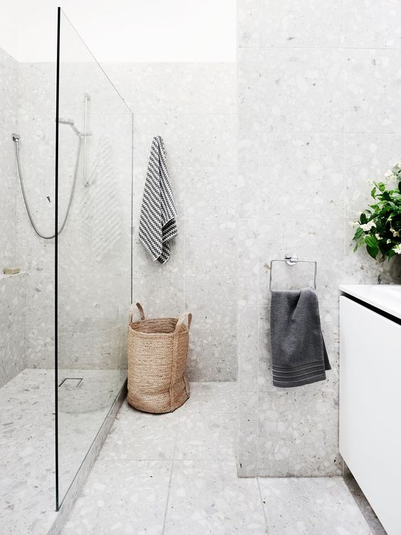 a beautiful neutral bathroom done with grey terrazzo, a basket, a white vanity and white appliances