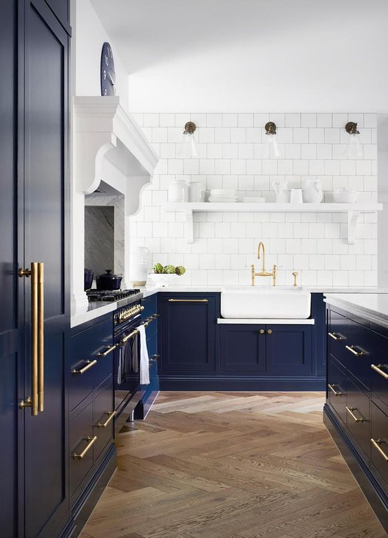 a classic Shaker-style kitchen in navy, with a white square tile backsplash and white stone countertops plus gold touches