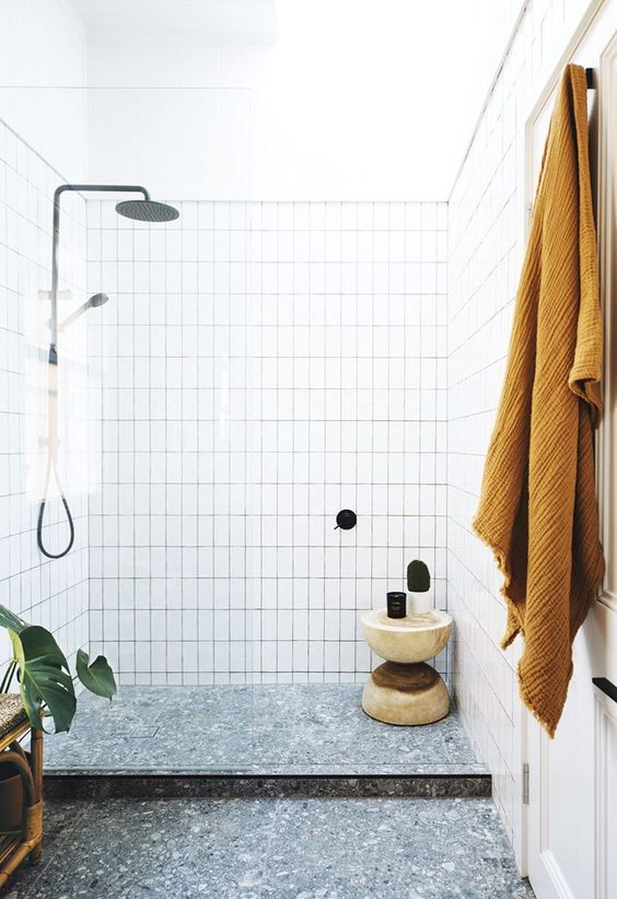 59 a chic and simple bathroom with white tiles, a grey terrazzo floor, mustard textiles and potted plants plus black fixtures
