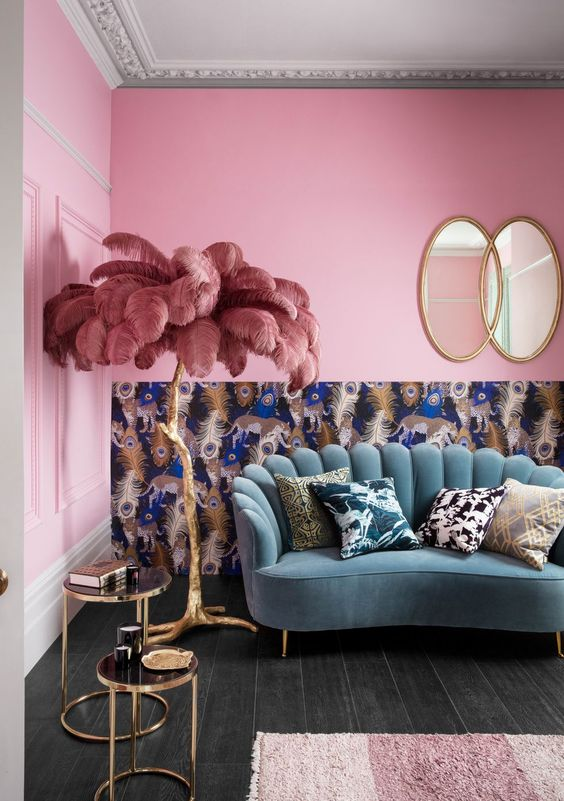 a colorful and whimsical living room with bright pink walls, a blue sofa, a peacock feather wall and a feather lamp