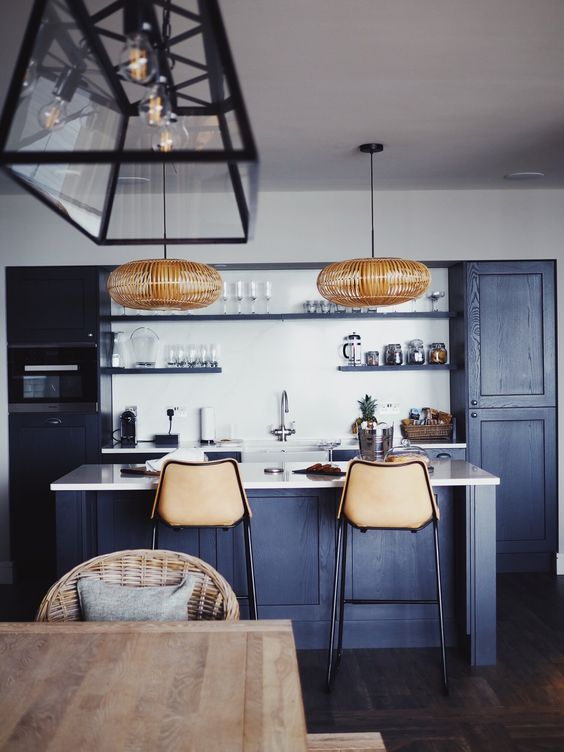 a cool contemporary navy kitchen with white countertops and a backsplash, rattan lamps and leather stools