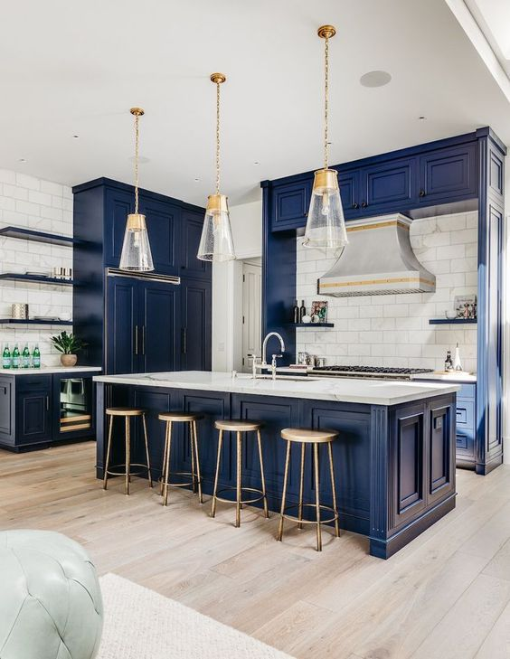 a beautiful navy kitchen with vintage cabinets, white marble countertops, a white tile backsplash and cool pendant lamps
