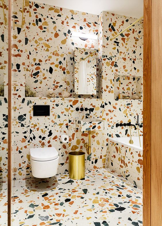 60 a bright terrazzo bathroom done with gold fixtures and a mirror plus a wall sconce over it