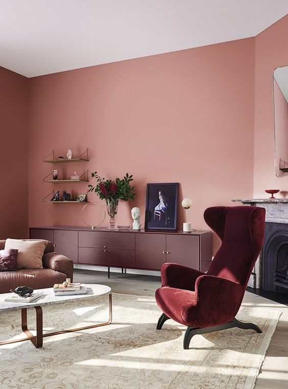 60 a pink living room complemented with a purple sideboard and a burgundy chair plus gold touches