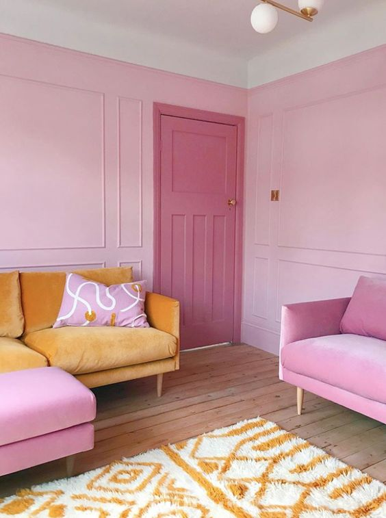 a bright pink living room with a yellow sofa and bold pink chairs, a bold pink door is super cool