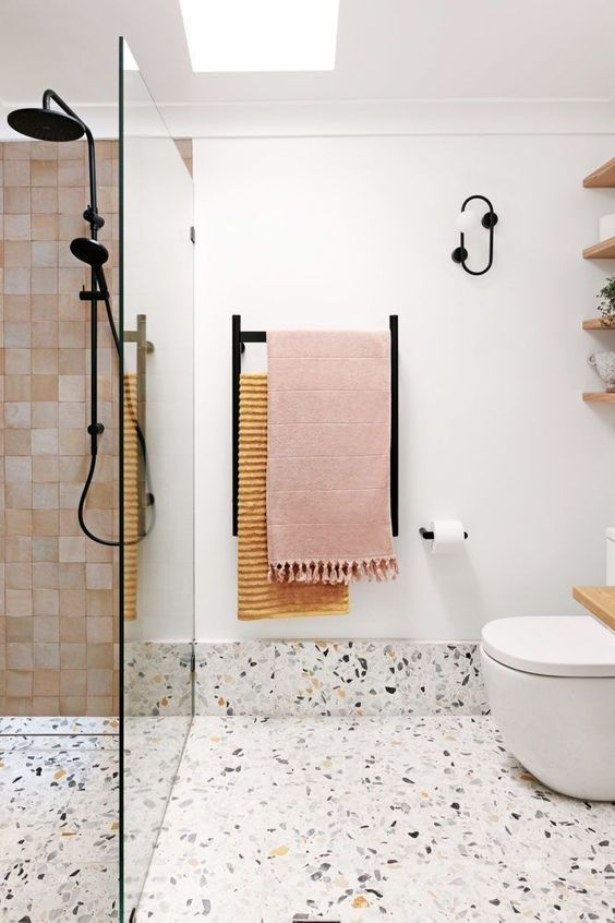 a contemporary bathroom with white tiles, a terrazzo floor, pink tiles, black fixtures and a skylight