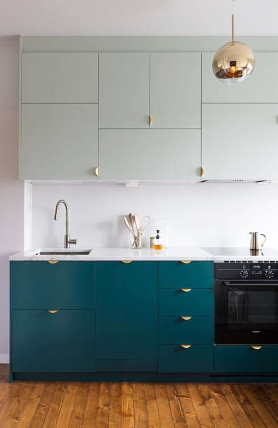 a stylish two tone kitchen in light green and teal, with gold handles, a copper pendant lamp and a white countertop and backsplash