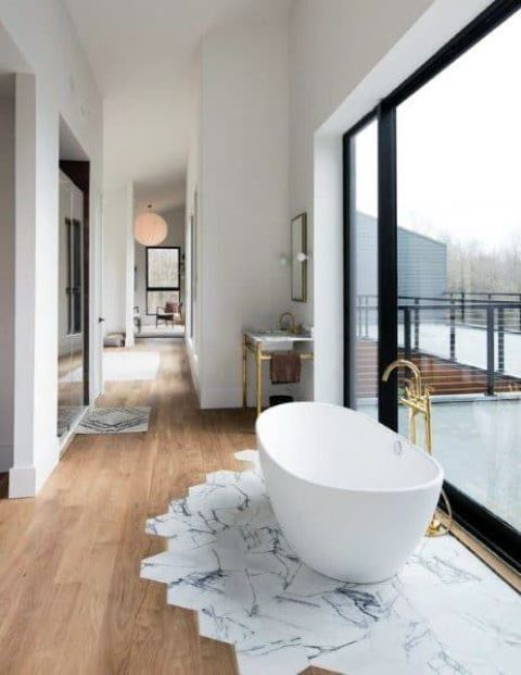 an airy bathroom with a glazed wall, a floor transition with marble and wood tiles and an oval bathtub