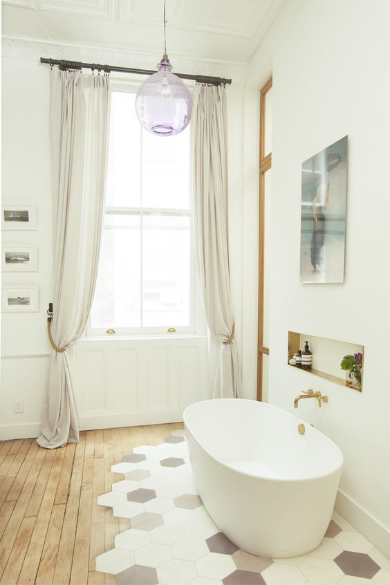 a refined bathroom with a wood floor and hex tiles, an oval tub, an artwork and a lilac pendant lamp