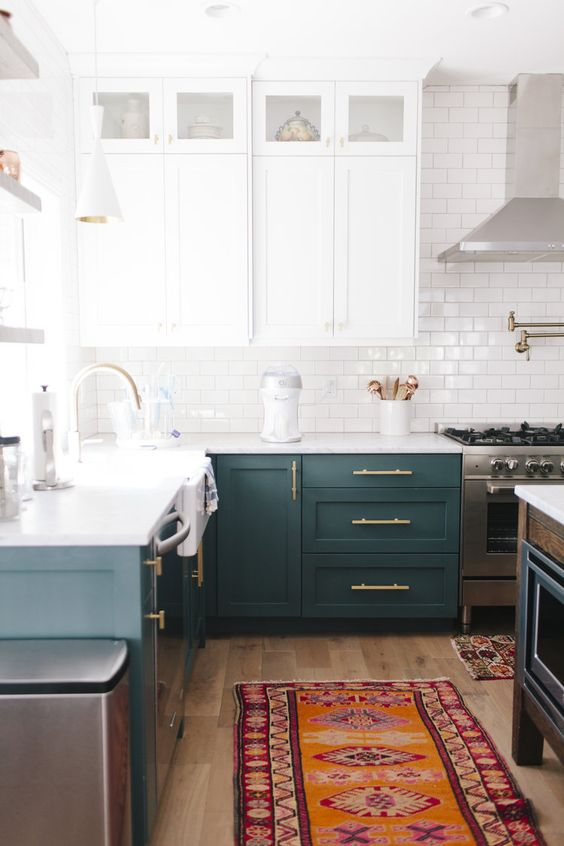 a stylish modern two tone kitchen with white and teal cabinets, a white subway tile backsplash, white countertops and a matching kitchen island