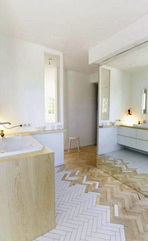 a chic contemporary bathroom in neutrals, with a wood and white tile floor, a floating vanity and a bathtub clad with wood