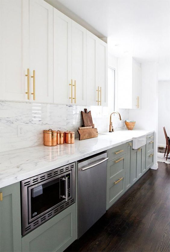 an elegant and shiny kitchen with white and sage green cabinetry, a white stone countertop and backsplash, gold touches