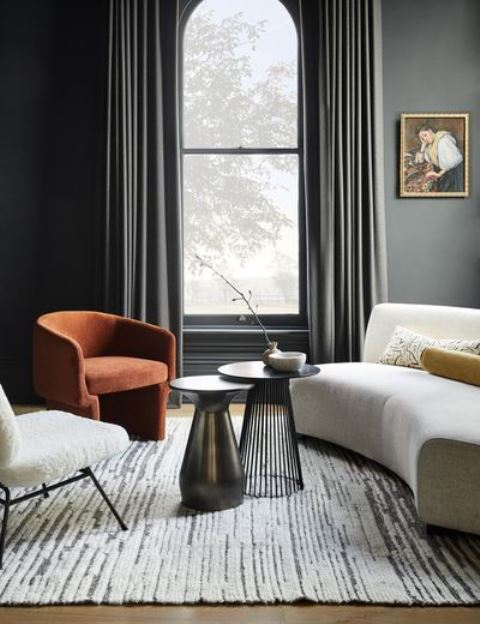 an exquisite and chic living room with grey walls, dark draperies, a curved sofa, a rust chair and a white one