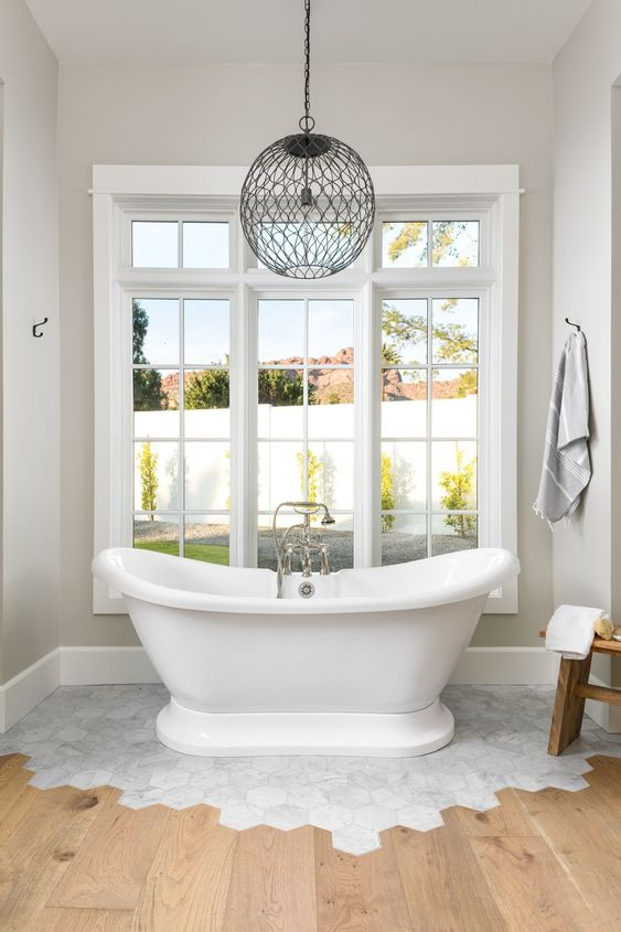 65 a vintage bathroom with neutral walls, a white marble hex tile floor and wooden floors plus a vintage bathtub and a pendant lamp