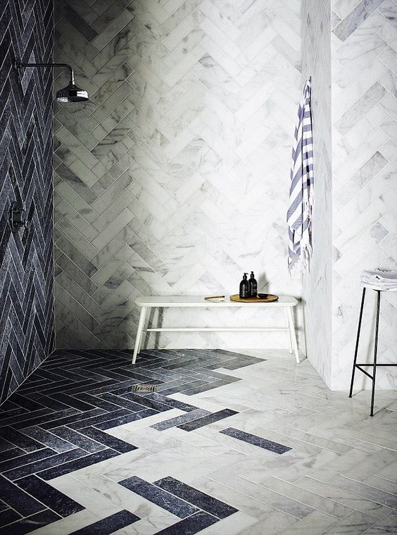 a chic bathroom with white marble tiles and navy ones, with a bench, a stool and neutral fixtures