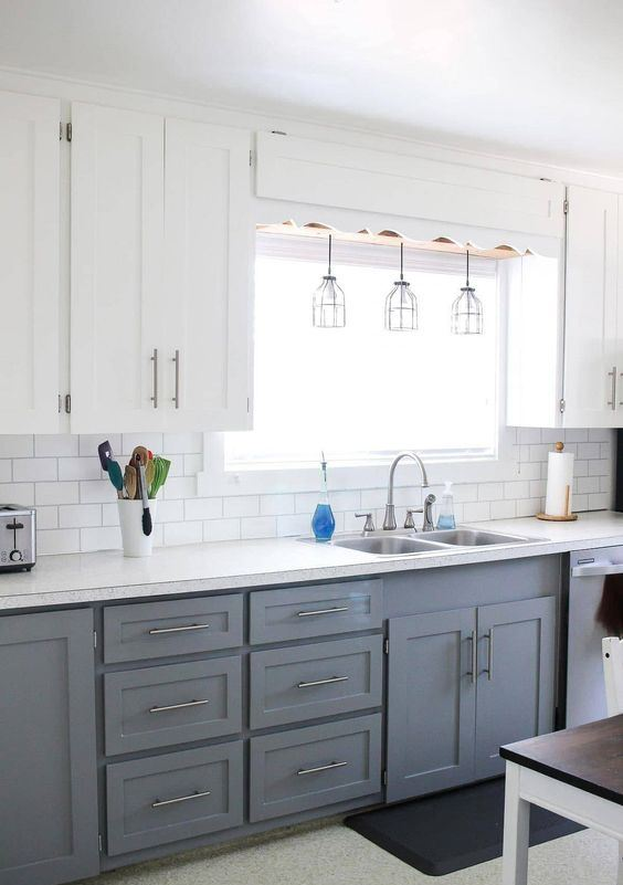 a modern two-tone farmhouse kitchen with white and grey cabinets, a white subway tile backsplash, white countertops and pendant lamps